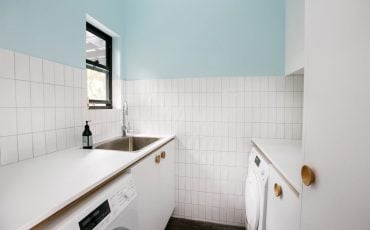laundry area with a very neat tiles and paint by grant wood painting