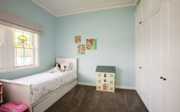 kiddie bedroom with single bed and a dollhouse one the side